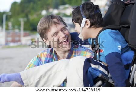 Father and disabled five year old son laughing together on beach - stock photo