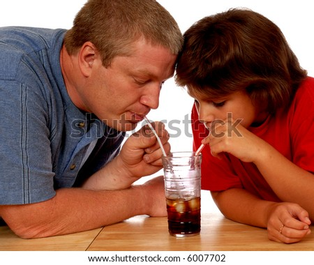 Father and elementary daughter sharing one iced drink together by drinking from two different straws. - stock photo