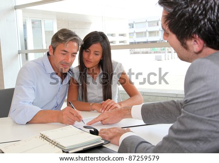 Father and girl signing loan contract - stock photo