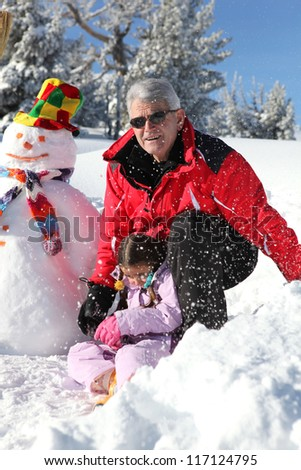 Father and grandfather building snowman - stock photo