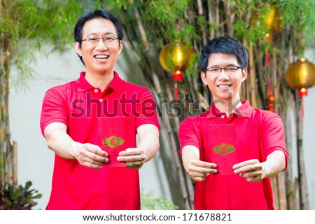 Father and grown up son celebrating Chinese new year with traditional gift, wearing red shirts - stock photo