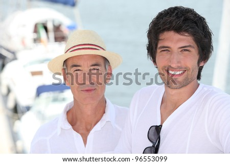 Father and grownup son at a marina - stock photo