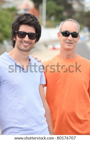 Father and grownup son wearing shades