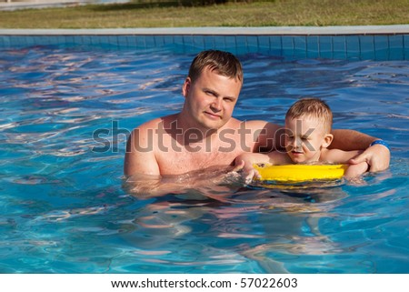 Father and happy son in swimming pool - stock photo