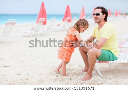 Father and his adorable little daughter at resort beach