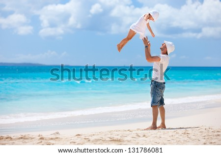 Father and his adorable little daughter at tropical beach having fun