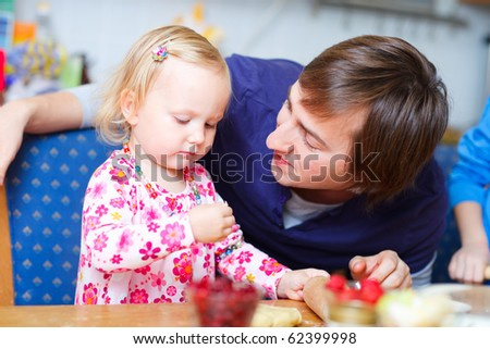 Father and his adorable little daughter baking together - stock photo
