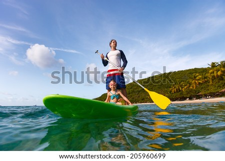 Father and his adorable little daughter paddling on stand up board having fun during summer beach vacation - stock photo