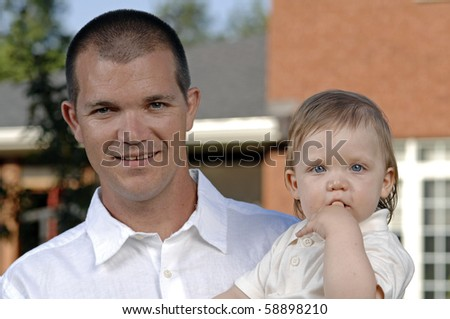 Father and his baby son play in the garden - stock photo