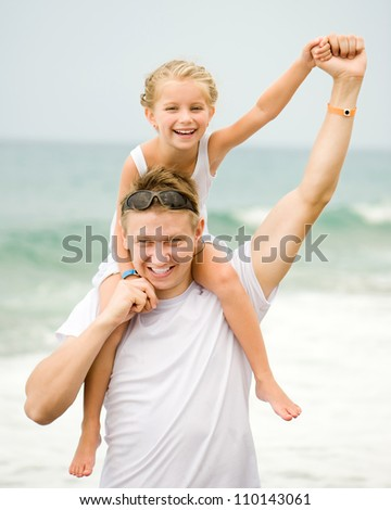 father and his cute little daughter on the beach - stock photo