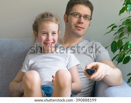Father and his daughter watching TV. - stock photo