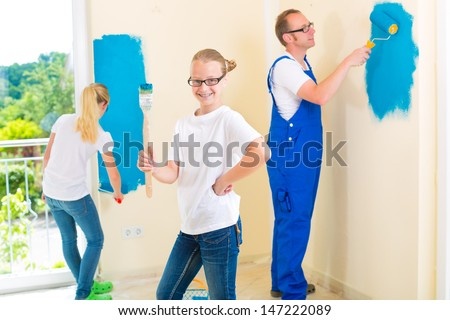 Father and his daughters or daughter with her friend are painting with paint roller a wall in blue. - stock photo