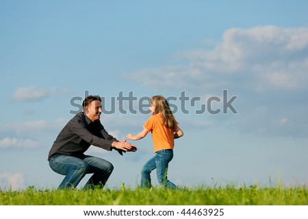 Father and his kid - daughter - playing together at a meadow, at a late summer afternoon, family concept