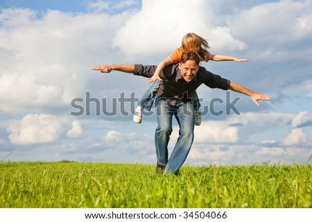 Father and his kid - daughter - playing together at a meadow, he is carrying her piggyback - stock photo