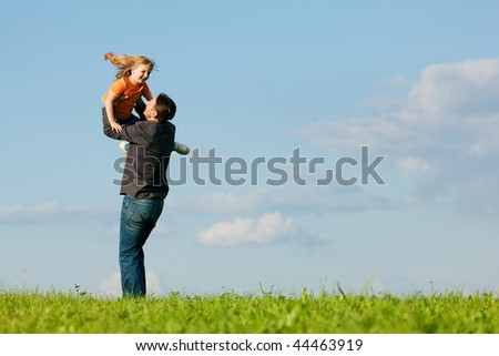 Father and his kid - daughter - playing together at a meadow, he is throwing her into the air at a late summer afternoon, family concept - stock photo