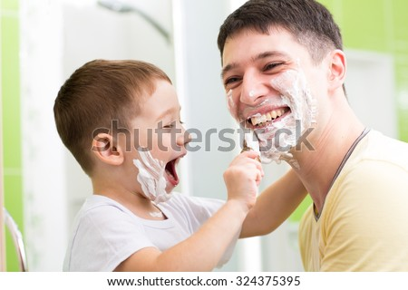Father and his kid son playing in bathroom. Child boy putting shaving cream on dad face - stock photo