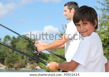 father and his little boy fishing - stock photo