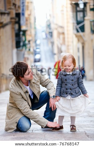 Father and his little daughter outdoors in city - stock photo
