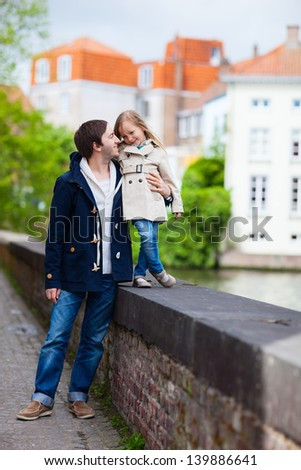 Father and his little daughter outdoors in city on a spring day - stock photo