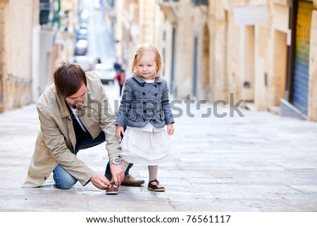 Father and his little daughter outdoors in city on sunny spring day - stock photo