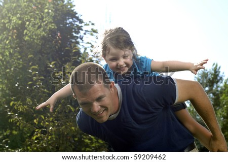 Father and his little daughter play in the backyard.