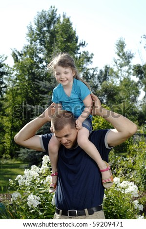 Father and his little daughter play in the backyard. - stock photo