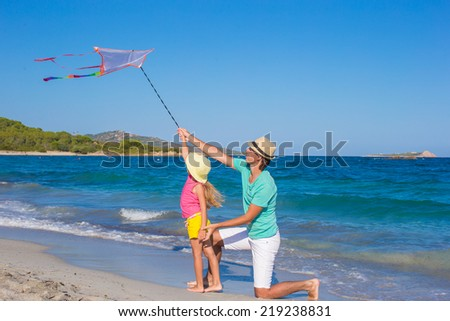 Father and his little daughter playing with a kite