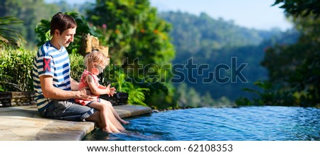 Father and his little daughter sitting at edge of swimming pool