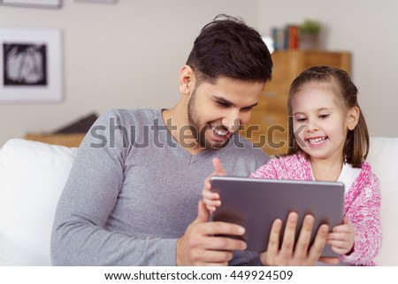 Father and his little daughter using a tablet computer grinning as they look at something on the screen together while relaxing on a sofa