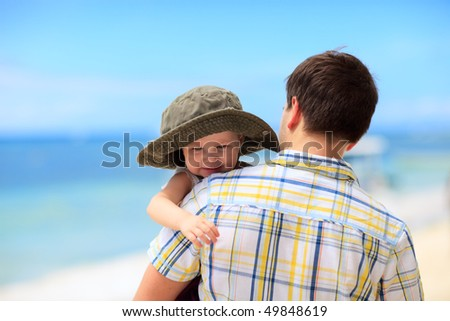 Father and his little daughter walking along tropical beach - stock photo