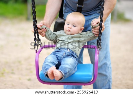 Father and his little son having fan on a swing at summer day - stock photo