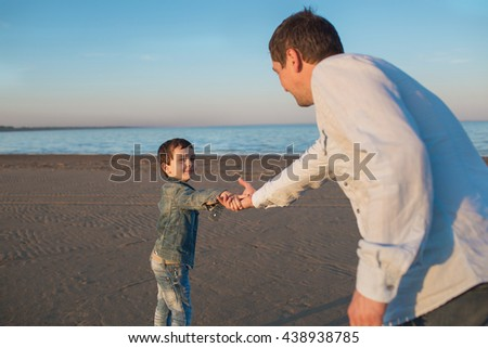 Father and his little son hold their hands on a beach in the evening - stock photo