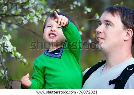 Father and his little son outdoors in spring park - stock photo