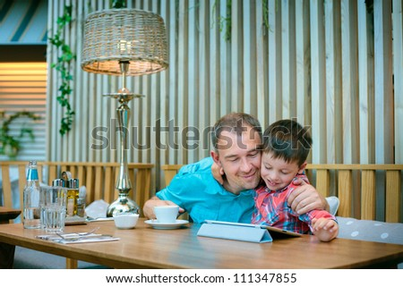 Father and his little son relaxing  and looking at laptop screen in cafe - stock photo