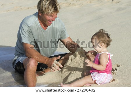 Father and his 11 months daughter playing with sand on the beach. - stock photo