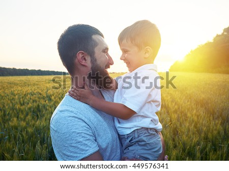 Father and his small son are looking at each other and smiling during magnificent sunset in the field