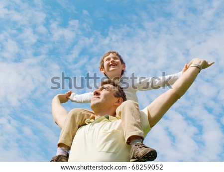Father and his son against the cloudy sky - stock photo