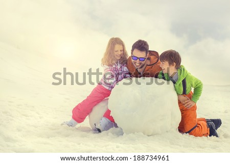 father and his son and doughter building a snowman, snow - stock photo