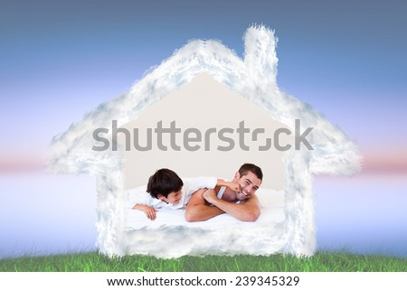 Father and his son having fun on a bed against green grass under blue and purple sky - stock photo