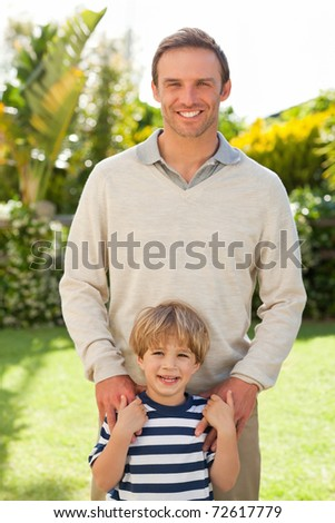 Father and his son looking at the camera in the garden - stock photo