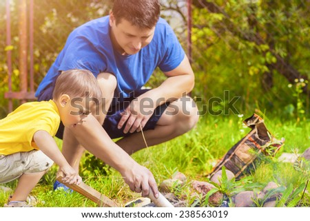 Father and His Son Making Fireplace Together Outdoors.Horizontal Image - stock photo