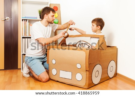 Father and his son making toy car of cardboard box - stock photo