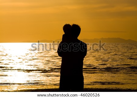 Father and his son on the Beach - Silhouette - stock photo