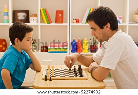 Father and his son playing chess - stock photo