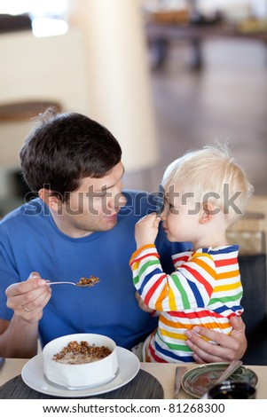 father and his son playing hide and seek while having a breakfast - stock photo