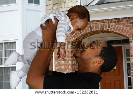 Father and his son playing outside in their yard - stock photo
