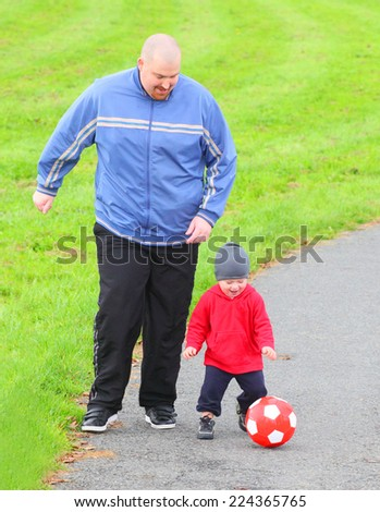 Father and his son playing together with soccer ball. - stock photo