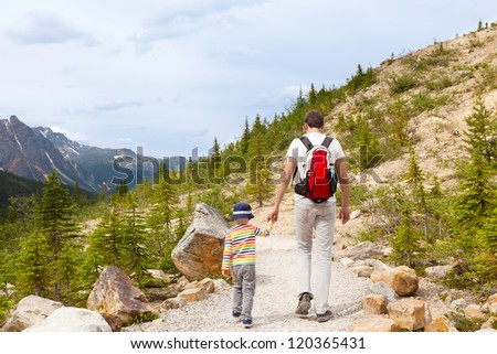 father and his son walking in a national park - stock photo