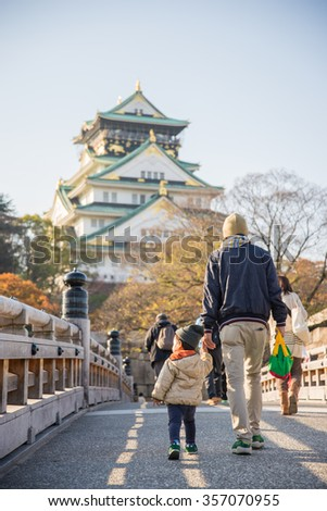Father and his son walking on pathway to Osaka Castle in Japan - stock photo
