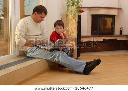 Father and his son with laptop in a room